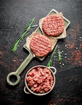 Hamburger crudi con carne macinata e rosmarino. sul tavolo rustico scuro