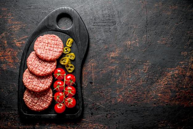 Hamburger crudi con peperoncini jalapeno e pomodori. su fondo rustico scuro
