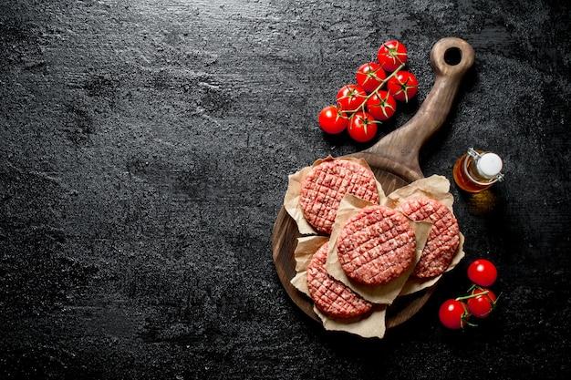 Hamburger crudi con olio e pomodori sul ramo. su sfondo nero rustico