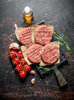 Hamburger crudi con pomodori, rosmarino e olio. su superficie rustica scura