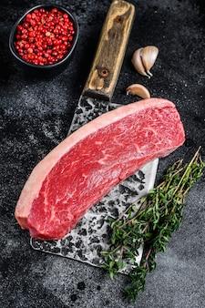 Bistecca di carne di manzo di berretto crudo su una mannaia da macellaio sulla tavola di legno. vista dall'alto.