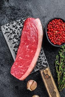 Bistecca di carne di manzo di berretto crudo su una mannaia da macellaio.