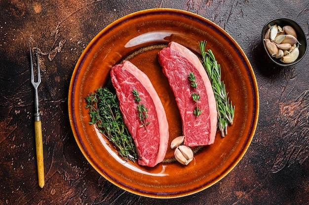 Bistecca cruda di bistecca di carne di manzo picanha o brasiliana sulla tavola di legno. vista dall'alto.