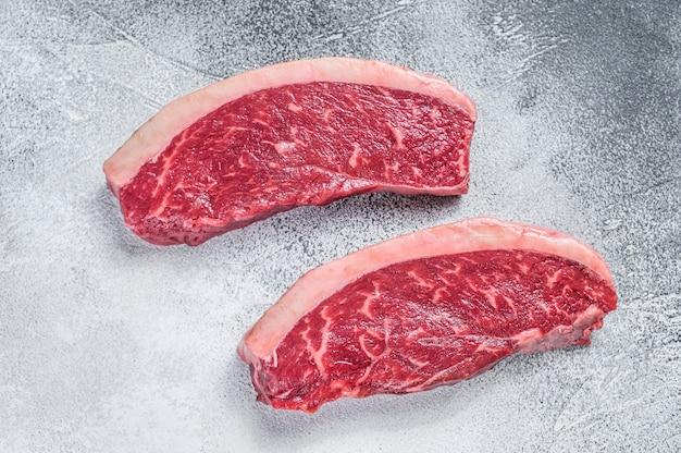 Bistecca di manzo cruda di bistecca di manzo o controfiletto su bianco. vista dall'alto.