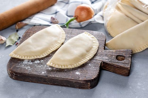 Chebureks crudi con carne, preparati per la frittura su una tavola di legno con farina, vista dall'alto, orizzontale