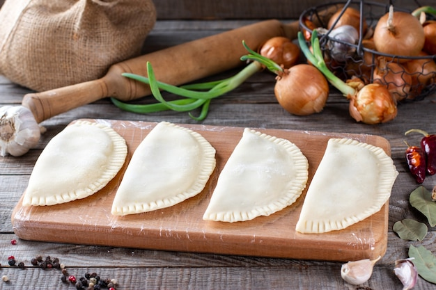 Chebureks crudi su uno sfondo di legno. il concetto di cottura in casa con pasta cruda e carne macinata, orizzontale