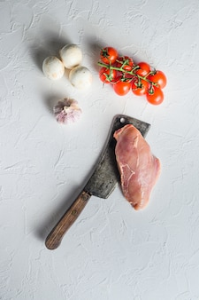 Petto di pollo crudo sul coltello da macellaio su sfondo bianco