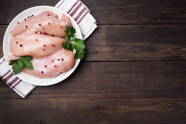 Filetto di petto di pollo crudo su un piatto, fondo di legno scuro. vista dall'alto, copia spazio