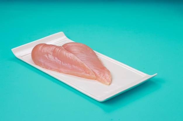 Filetto di petto di pollo crudo senza pelle disposto su stoviglie piatte a forma di rettangolo bianco