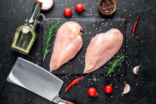 Petti di pollo crudi con ingredienti sul tavolo di pietra
