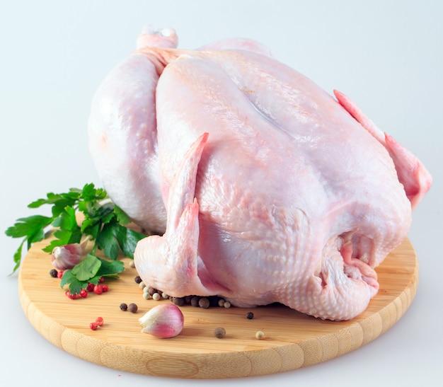 Carcassa di pollo crudo sul tagliere isolato su bianco