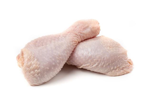 Cosce di pollo crude, isolate su fondo bianco.