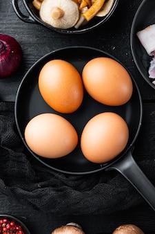 Uova di gallina crude nel set di scatole per uova, sul fondo della tavola in legno nero, vista dall'alto laici piatta