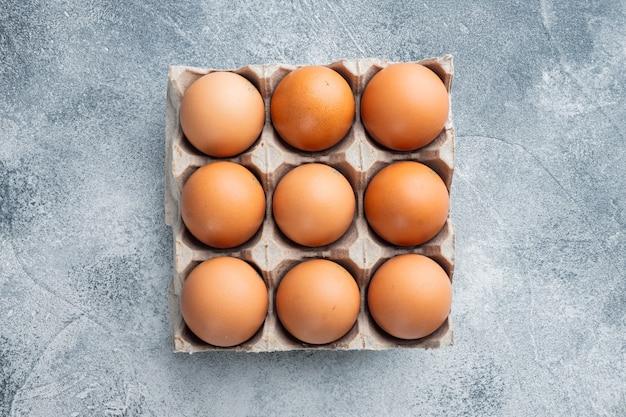 Uova di gallina crude in scatola per uova impostato su sfondo grigio, vista dall'alto laici piatta