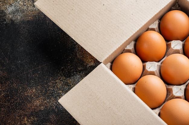 Uova di gallina crude in scatola per uova insieme, sul vecchio fondo rustico scuro, vista dall'alto laici piatta, con spazio per il testo copyspace