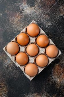 Uova di gallina crude in scatola per uova insieme, sul vecchio fondo rustico scuro, vista dall'alto laici piatta
