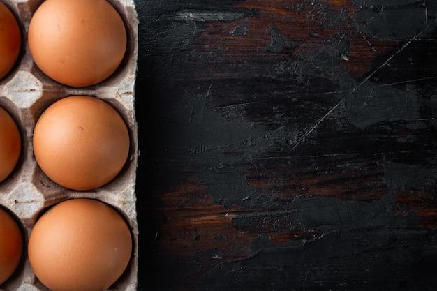 Uova di gallina crude in scatola per uova insieme, sul vecchio fondo di tavola in legno scuro, vista dall'alto laici piatta,