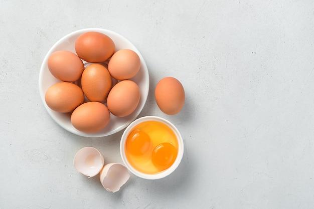 Uova di gallina crude e tuorli d'uovo su uno sfondo di cemento grigio. vista dall'alto, copia dello spazio.