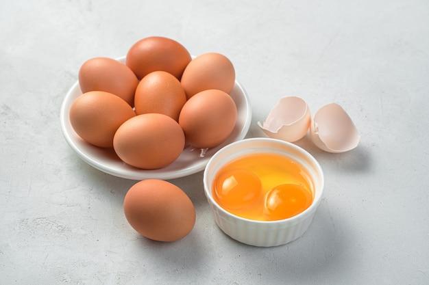 Uova di gallina crude e due tuorli su sfondo grigio