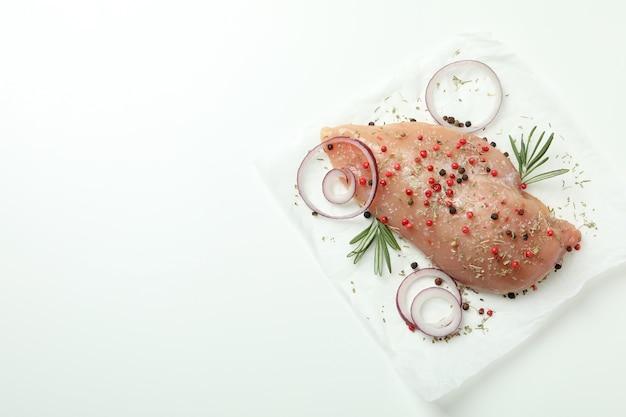 Filetto di pollo crudo con ingredienti su sfondo bianco