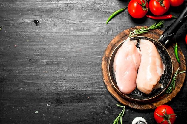 Filetto di pollo crudo con pomodori ed erbe aromatiche. sulla lavagna nera.
