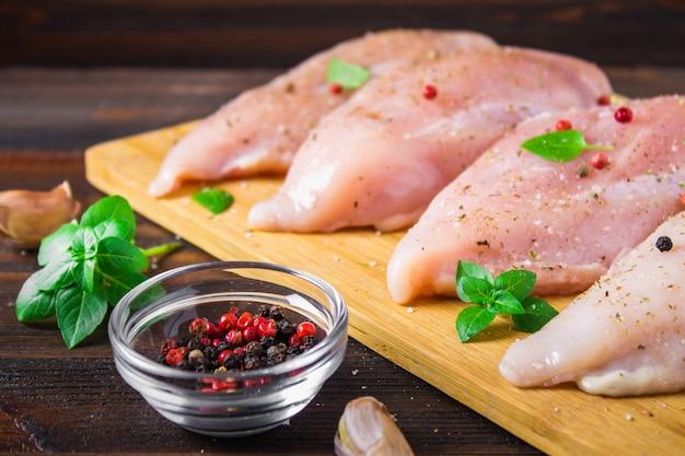Filetti di pollo crudo su un tagliere sullo sfondo di un tavolo di legno.
