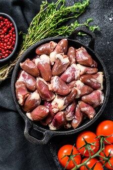 Cuori di pollo crudi in padella. frattaglie organiche. sfondo nero. vista dall'alto.