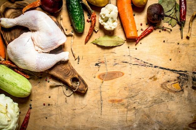 Coscia di pollo crudo con verdure per cucinare la zuppa