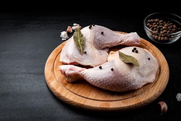 Cosce di pollo crudo su sfondo nero.
