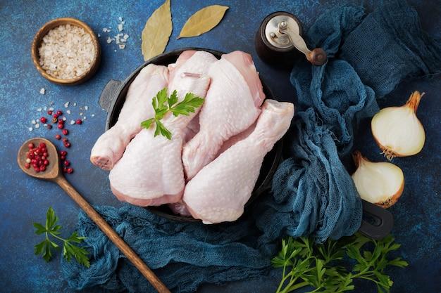 Cosce di pollo crude su una pentola di ghisa con spezie ed erbe aromatiche su un cemento scuro o una pietra preparata per la cottura.