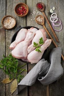 Cosce di pollo crude su una pentola in ghisa con spezie ed erbe aromatiche su legno vecchio preparato per la cottura.