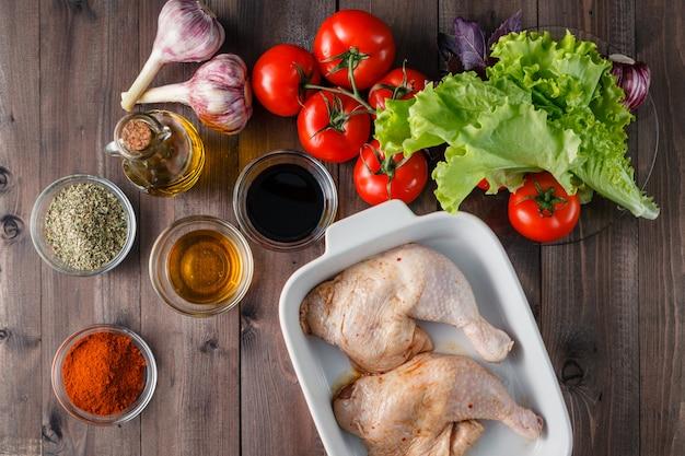 Cosce di pollo crude ed ingredienti di marinata sul bordo della cucina