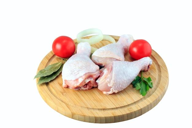 Cosce di pollo crude su sfondo bianco