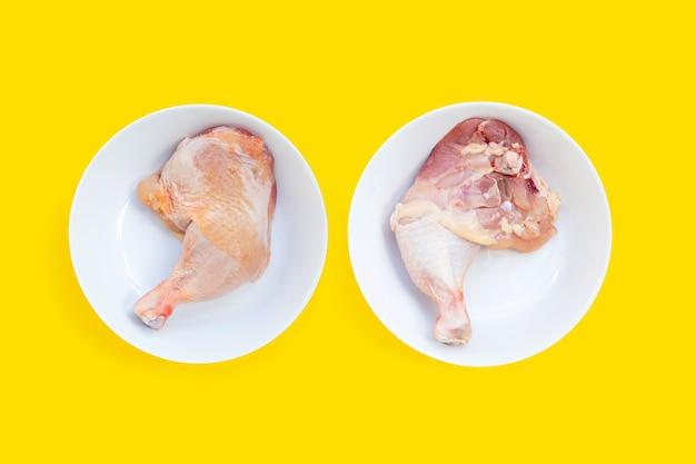 Cosce di pollo crude in piatti bianchi su sfondo giallo.