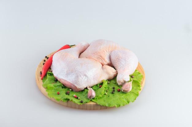 Cosce di pollo crude su un bianco