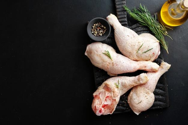 Cosce di pollo crude con spezie a bordo su superficie scura