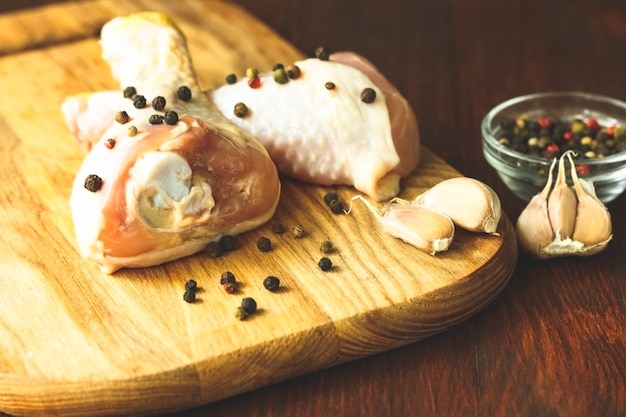 Cosce di pollo crude con spezie su fondo di legno