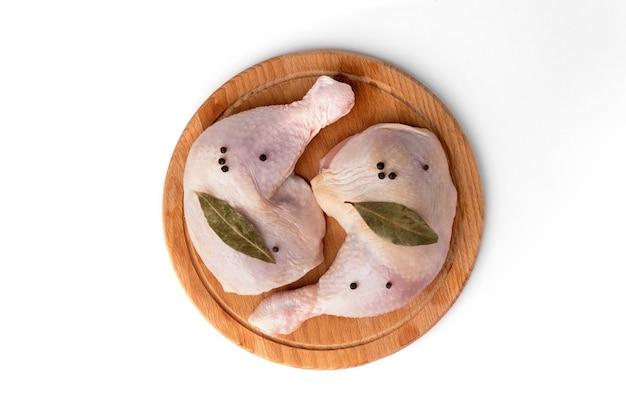 Cosce di pollo crudo sulla tavola di legno isolato su priorità bassa bianca.