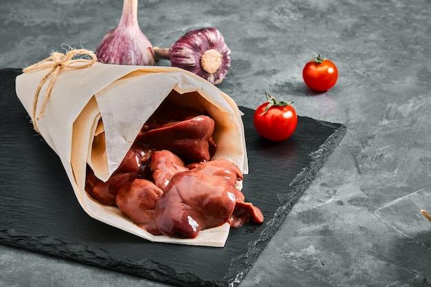 Filetto di fegato di pollo crudo su sfondo grigio cemento