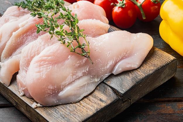 Tagli di carne di pollo crudo, sul vecchio tavolo in legno scuro