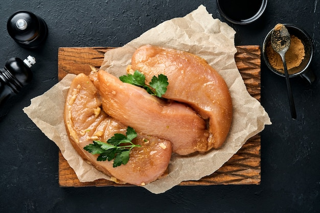 Filetto di carne di pollo crudo marinato in salsa di soia teriyaki, cipolle, aglio e pepe in piastra nera su uno sfondo scuro di ardesia, pietra o cemento. vista dall'alto con copia spazio.