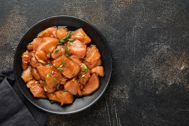 Carne di pollo cruda marinata in salsa di soia teriyaki, cipolle e pepe in un piatto nero su una superficie di cemento scuro