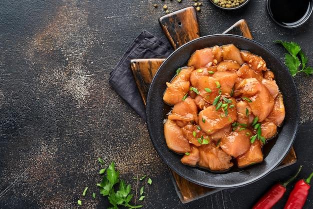 Carne di pollo cruda marinata in salsa di soia teriyaki, cipolle e pepe in un piatto nero su uno sfondo scuro di ardesia, pietra o cemento. vista dall'alto con copia spazio.