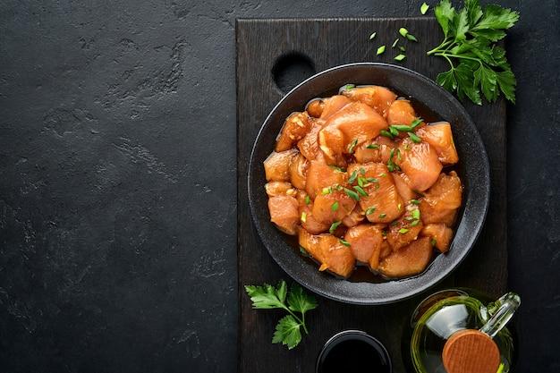 Carne di pollo cruda marinata in salsa di soia teriyaki, cipolle e pepe in un piatto nero