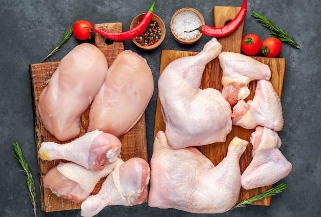 Carne di pollo cruda con varie parti di filetto, ali, cosce su sfondo concreto