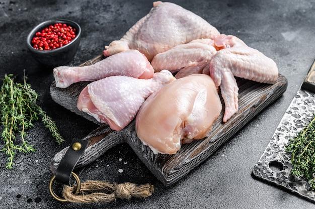 Porzioni di pollo crude per cucinare e grigliare con petto senza pelle, coscia e ali. vista dall'alto.