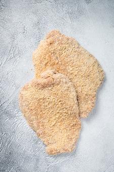 Cotoletta di pollo cruda scaloppina nel pangrattato. sfondo bianco. vista dall'alto.