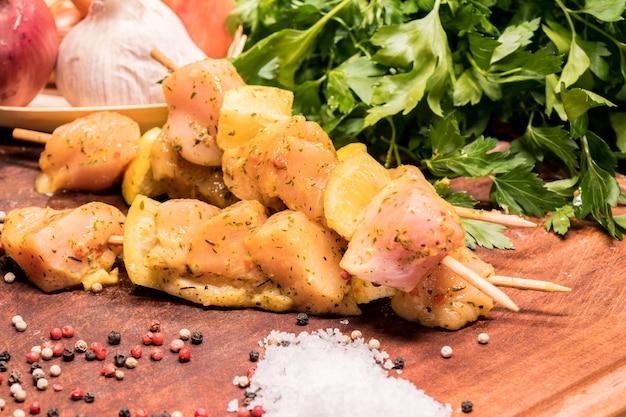 Spiedini di pollo crudi marinati al limone su una tavola di legno