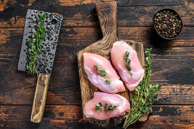 Filetto di coscia di pollo crudo senza pelle su un tagliere di legno. sfondo nero. vista dall'alto.