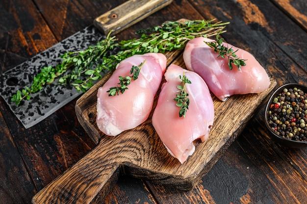 Filetto di coscia senza pelle di pollo crudo su un tagliere di legno.